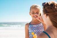 Kind wird von seiner Mutter am Strand eingecremt.