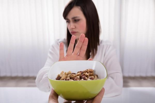 Frau lehnt Schale mit Nüssen ab