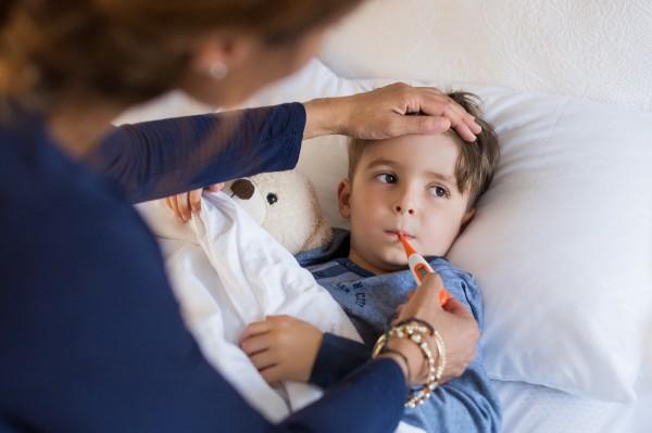 Kind liegt krank im Bett während die Mutter Fieber miest.