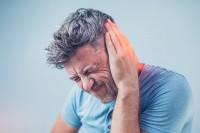 Mann mit Rauschen im Ohr hält sich das Ohr zu.