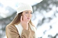 Frau fasst sich beim Winterspaziergang an ihre trockene Haut im Gesicht.