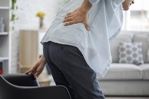 Mann hält sich beim Aufstehen den Rücken wegen plötzlicher Rückenschmerzen