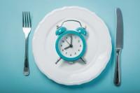 Uhr auf einem gedeckten Teller, um das Thema Heilfasten darzustellen