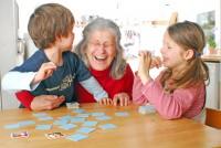 Ältere Frau nutzt Memory mit ihren Enkeln als Gedächtnistraining