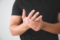 Mann hält sich die rheumatischen Finger.