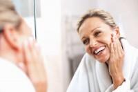 Frau steht vor dem Spiegel und schaut sich ihre Falten an Hals, Gesicht und Decolté an.