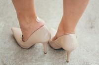 Frau auf Pumps zieht den Schuh aus und zeigt ihre Blase am Fuß.