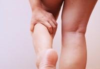 Frau mit Wasser in den Beinen greift sich an Unterschenkel