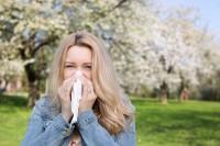 Frau putzt sich aufgrund von Heuschnupfen und Allergie im Freien die Nase.