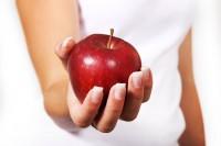 Frau mit rotem Apfel in der Hand