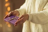 Frau im weißen Pullover überreicht eine ihrer Geschenkideen.