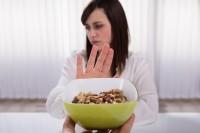 Frau mit Lebensmittelunverträglichkeit oder Lebensmittelallergie lehnt Nüsse ab