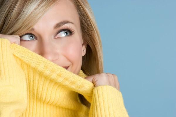 Frau versteckt Ihre Akne im Gesicht unterm Pullover