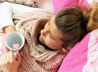 Frau liegt mit einer Tasse Tee im Bett