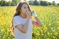 Frau nutzt Nasenspray im Sommer auf dem Feld.