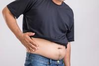 Mann mit Fettleber durch ungesunde Ernährung oder andere Faktoren hält sich den Bauch.