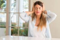 Frau ohne Gehörschutz hält sich die Ohren zu